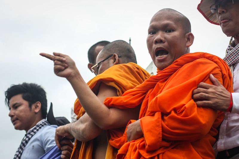 Soeung Hai shouts from atop a post demarcating the boundary between Cambodia and Vietnam in Svay Rieng province during an opposition-led protest in July. (Alex Willemyns/The Cambodia Daily)