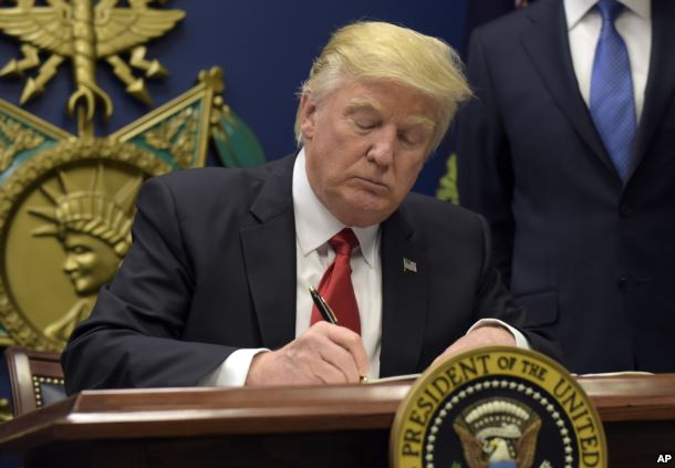 FILE - President Donald Trump signs an executive order on extreme vetting during an event at the Pentagon in Washington, Jan. 27, 2017.