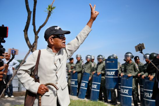 A man walks in front of riot police yesterday in Phnom Penh. Hong Menea