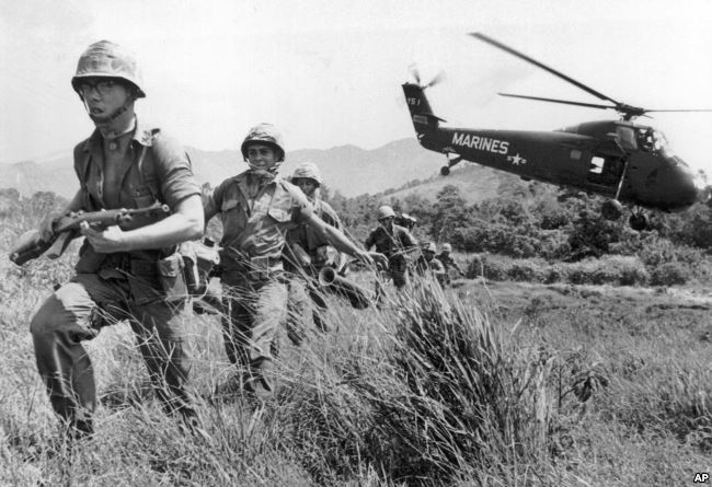 FILE - In this April 28, 1965 file photo, U.S. Marine infantry stream into a suspected Viet Cong village near Da Nang in Vietnam during the Vietnamese war. Filmmaker Ken Burns said he hopes his 10-part documentary about the War, which begins Sept. 17, 2017. Photo: VOA