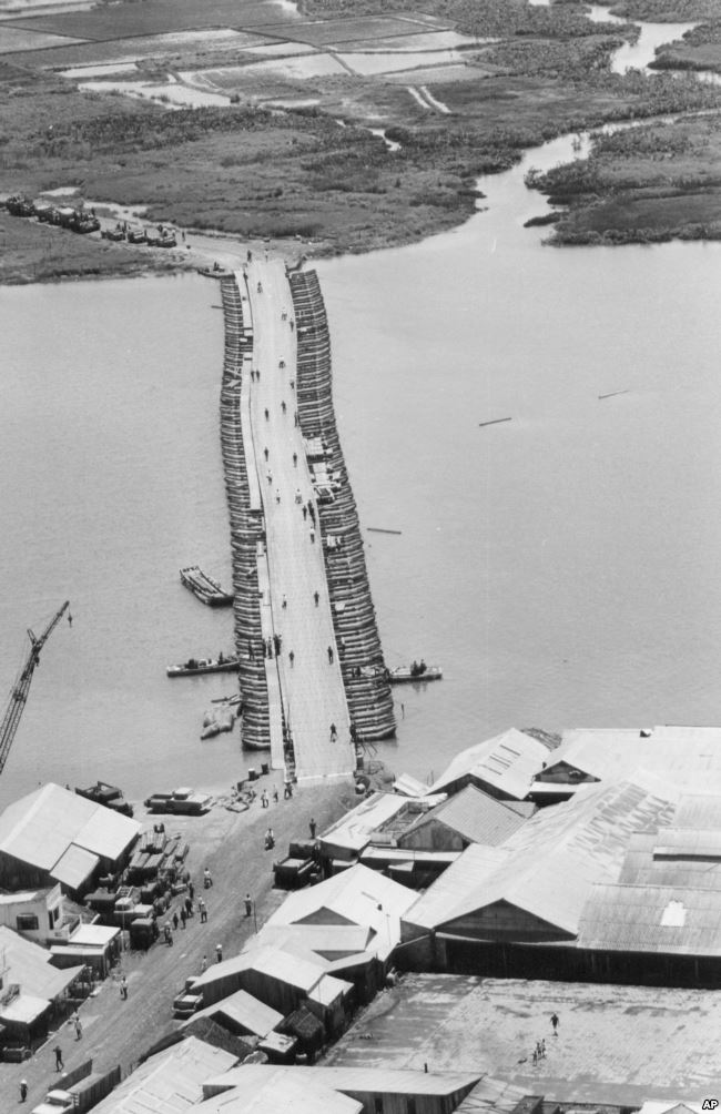FILE - Military traffic is halted as U.S. Army engineers finish repairing a pontoon bridge damaged by a Viet Cong underwater mine, August 1968. Linking Saigon with the Mekong Delta, the bridge over the Oriental River replaced the permanent bridge, blown up by the enemy. Photo: VOA